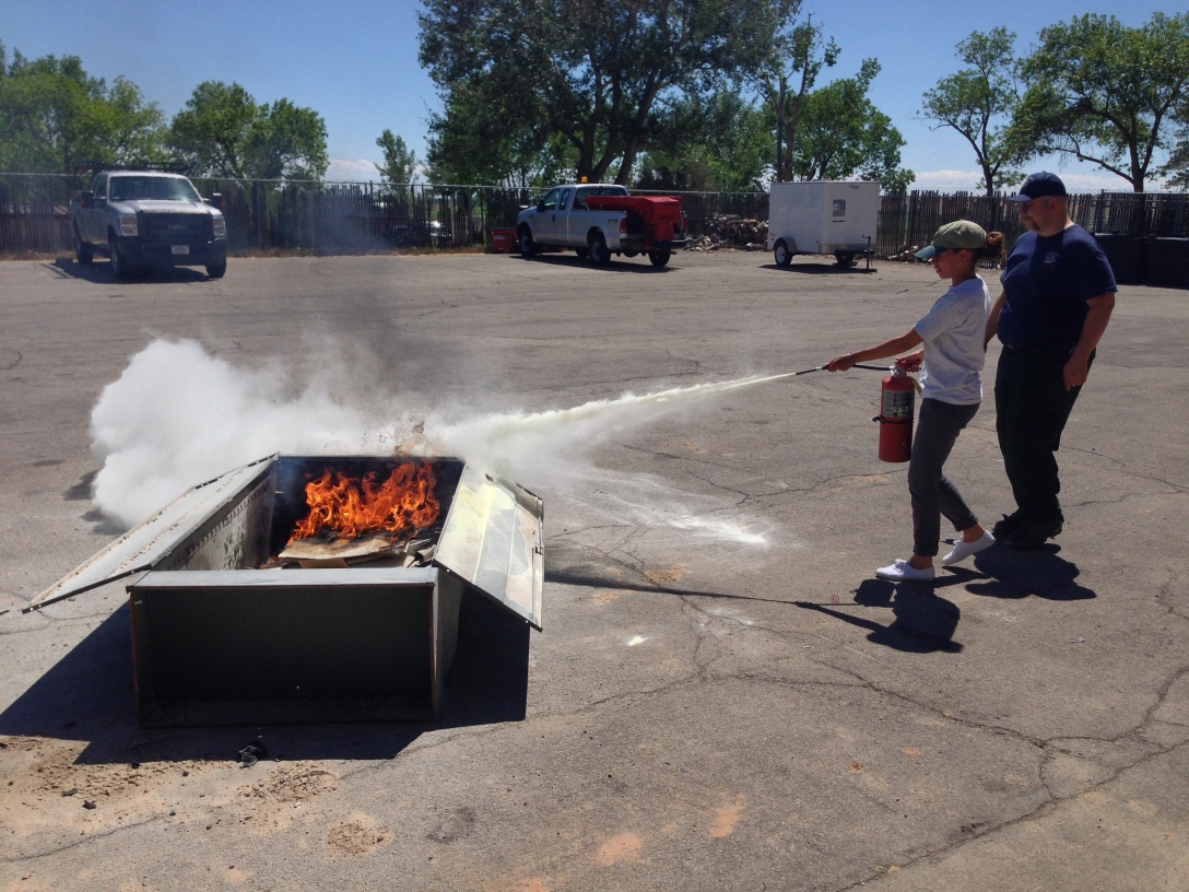 Marie Jimenez sweeps the the stream of a fire extinguisher toward the base of the flames as she was instructed by Larry Smith (right), Dinosaur National Monument fire ranger.