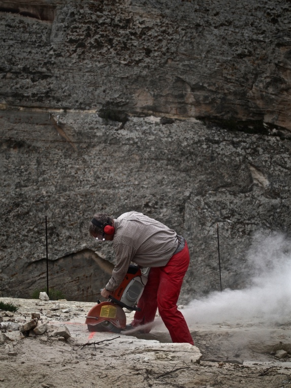 Paleontologist Brooks Britt cuts along the quarry's grid lines to create blocks, which will be prepped in a lab to uncover the fossils they contain.